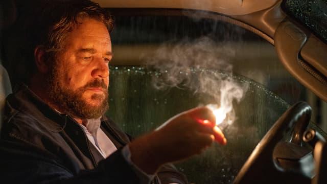 """""""Der Mann"""" (Russell Crowe) sitz am Steuer seines Autos und hält einen brennenden Zettel in der Hand."""