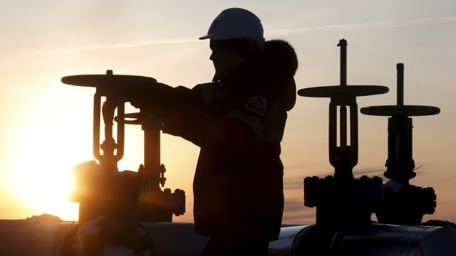 Ein Arbeiter kontrolliert das Ventil eines Ölrohrs in einem sibirischen Ölfeld.
