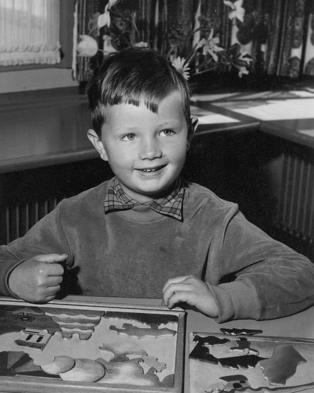 Ein Bub, der vor einem Holzpuzzle sitzt und in die Kamera lächelt.
