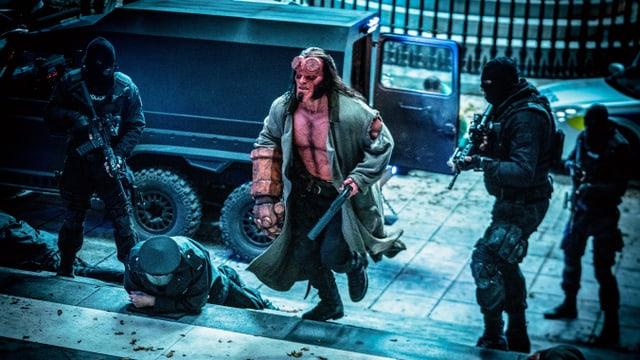 Hellboy schreitet eineTreppe hoch, bewacht von Scharfschützen