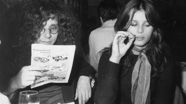 Zwei am Tisch. Er liest Zeitung, sie raucht.