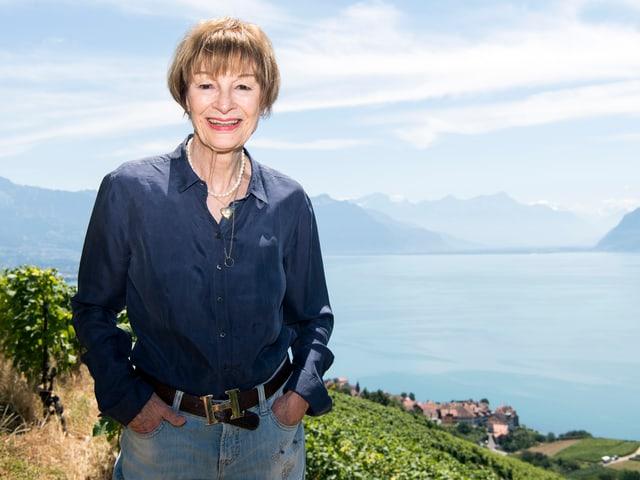 Frau posiert vor einer Kulisse bestehend aus See und Berge und lächelt in die Kamera.