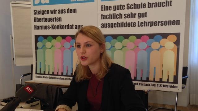 Saskia Olsson redend, dahinter zwei Plakate für die Initiativen.