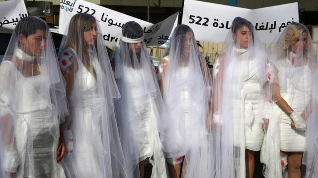 Frauen als Braut verkleidet mit blutigen Verbänden.
