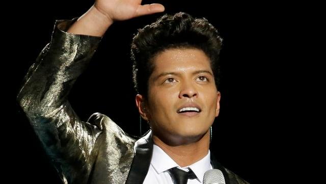 Bruno Mars auf der Bühne stehend.