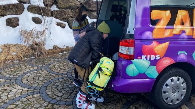 Gaël und Angela stehen vor dem violetten «Zambo-Bus» und legen das Snowboard in den Kofferraum.