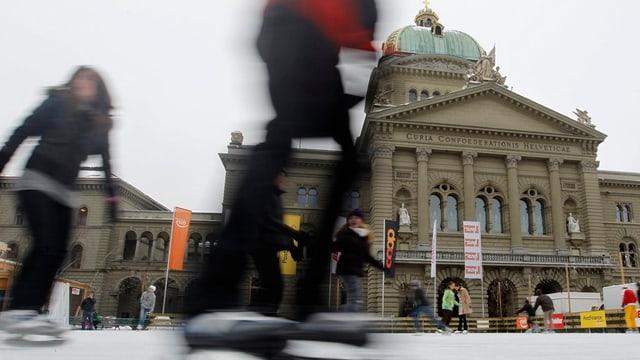 Schlittschuhläufer auf der Eisbahn vor dem Bundeshaus.