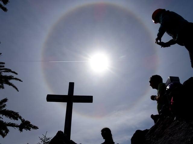 Ein Gipfelkreuz unter einem Halo.
