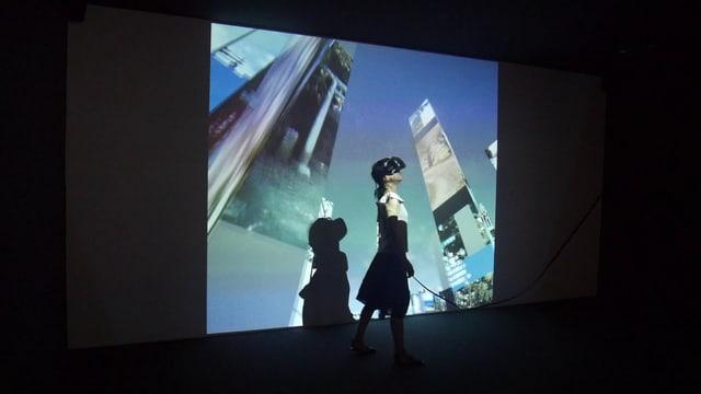 Eine Frau mit VR-Brille steht in einem dunklen Raum. Auf ihren Körper und an die Wand wird ein Bild projiziert, auf dem Wolkenkratzer zu sehen sind.