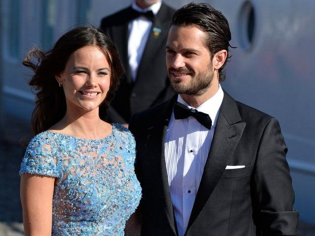 Frau in Kleid und Mann in Anzug posieren für die Kamera