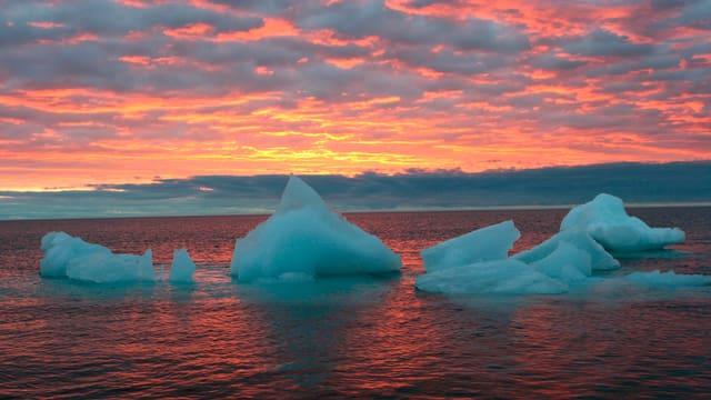 Symbolbild: Überreste eines Eisbergs treiben im Meer bei untergehender Sonne.