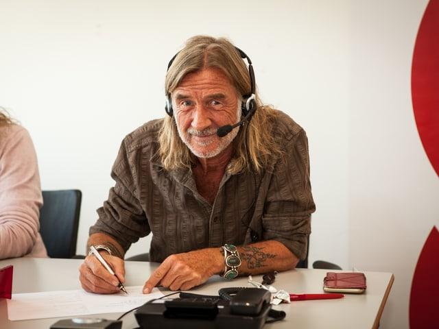 Mann mit langen Haaren und Tattoos am Telefon.