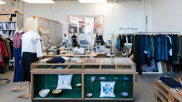 Blick auf das Atelier von Sabine Portenier. Es hat Kleider und Nähmaschinen im Atelier.