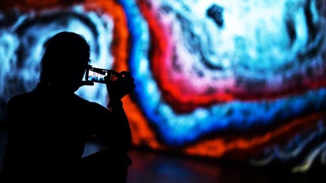 Ein Mann photographiert mit seinem Handy ein grosses Wandbild.