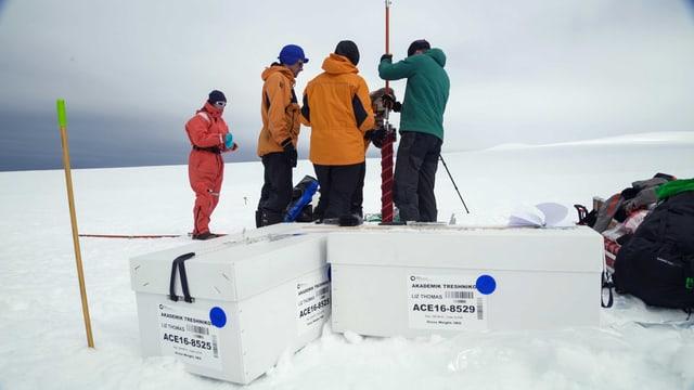 Vier Leute stehen in einer Schneelandschaft um eine Bohrstelle.