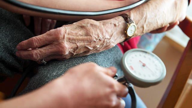 Eine Pflegerin nimmt einer alten Frau den Puls.