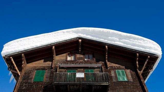 Altes Walliser Holzchalet mit Schnee auf dem Dach