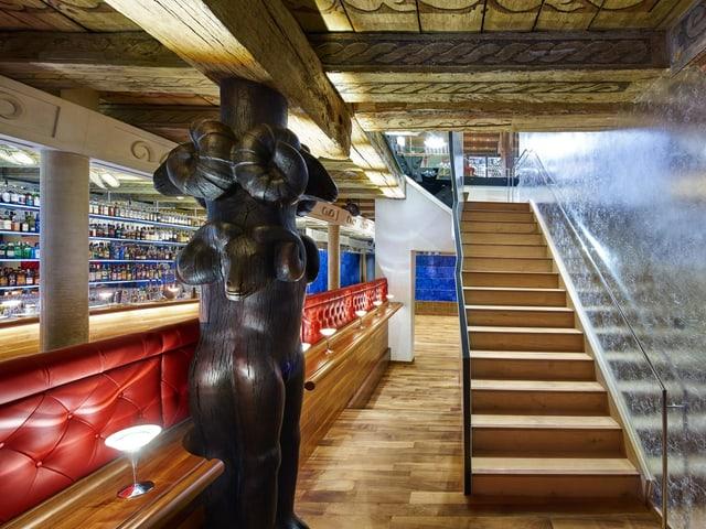 Raum in einem Holzgebäude mit einer langen Bar und einer Holztreppe mit gläsernem Geländer.