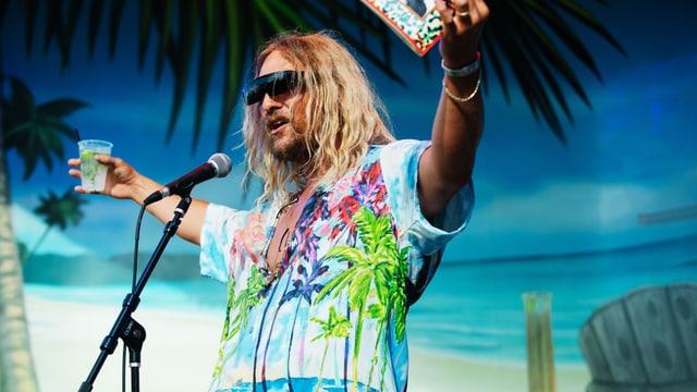 Mann auf Bühne im Hawaihemd mit Buch und Drink in der Hand.