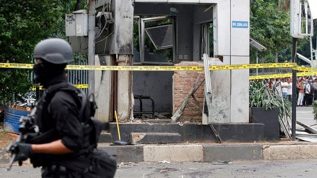 Vermummter Polizist vor einer zerstörten Fassade