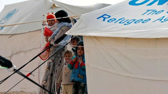 Personen zwischen UNO-Zelten.