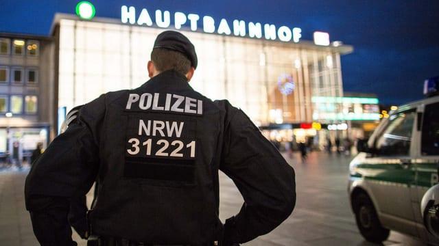 Polizist steht vor dem Kölner Hauptbahnhof.