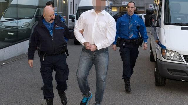 Polizisten führen einen Angeklagten vom Bus zum Gerichtssaal