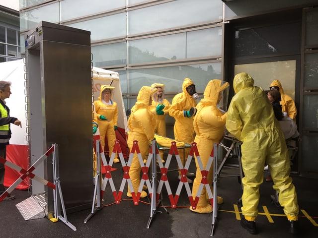 Mitarbeiter in gelben Schutzanzügen.