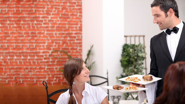 Ein lächelnder Kellner serviert eine Frau eine Speise