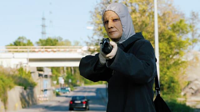 Ein maskierter Mann mit einer Schrotflinte.