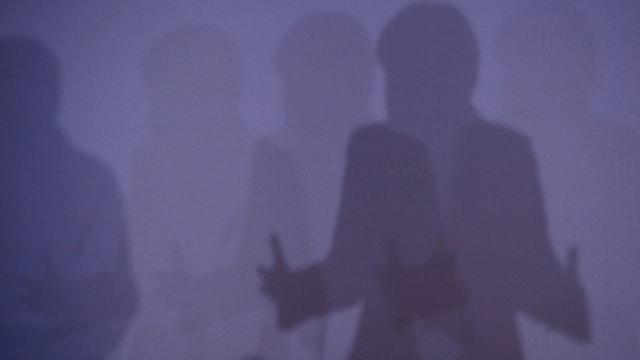 Der Schatten von Angela merkel auf einer violetten Wand.