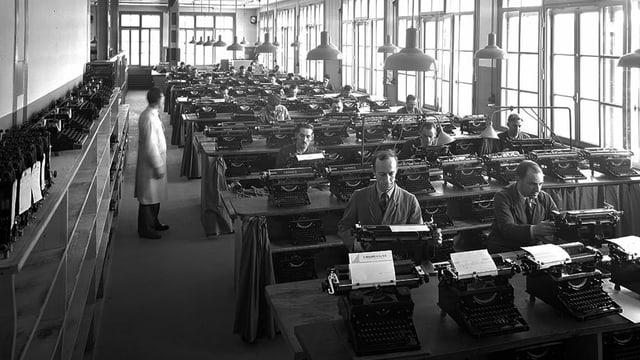 Schwarzweissfoto: In einem Fabrikraum sitzen an langen Bänken Menschen hinter Schreibmaschinen