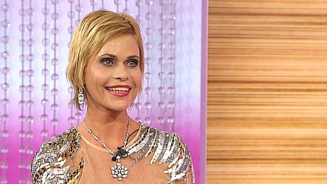 Eine blonde Frau mit kurzen blonden Haaren und Glitzerkleid lacht in die Kamera.