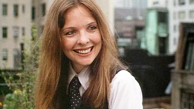 Frau lächelt auf einem Balkon in Manhattan und trägt eine Krawatte.