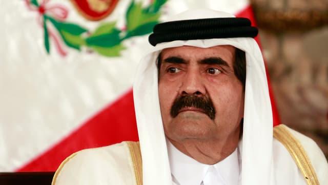 Portrait des Emirs von Katar vor einer Flagge.