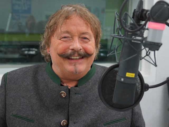 Mann mit auffälligem Schnurrbart im Studio hinter Mikrofon.