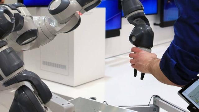 Eine Menschenhand greift eine Roboterhand.