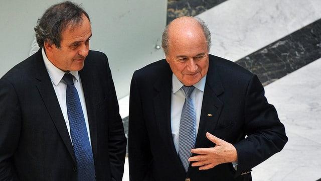 Platini und Blatter vor einer Marmorwand.