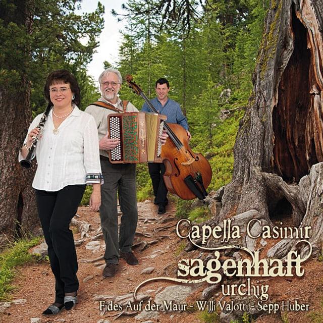Fides Auf der Maur mit Klarinette, Willi Valotti mit Schwyzerörgeli und Sepp Huber mit Kontrabass auf einem Waldweg, auf dem Cover zu ihrem Album «sagenhaft urchig».