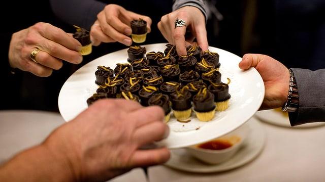 Vier Hände greifen nach Pralinés, die mit Mehlwürmer verziehrt sind, von einem weissen Teller.