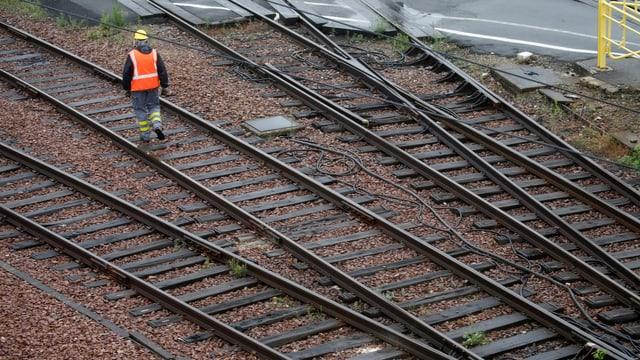 Ein Arbeiter mit Leuchtweste geht auf einem Bahngleis.