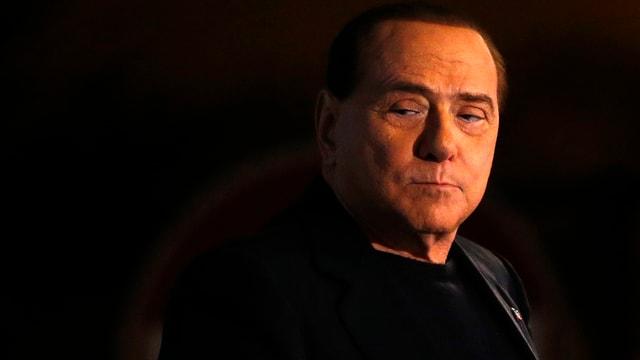 Nur Berlusconis Gesicht ist gut sichtbar, beleuchtet in der Dunkelheit.