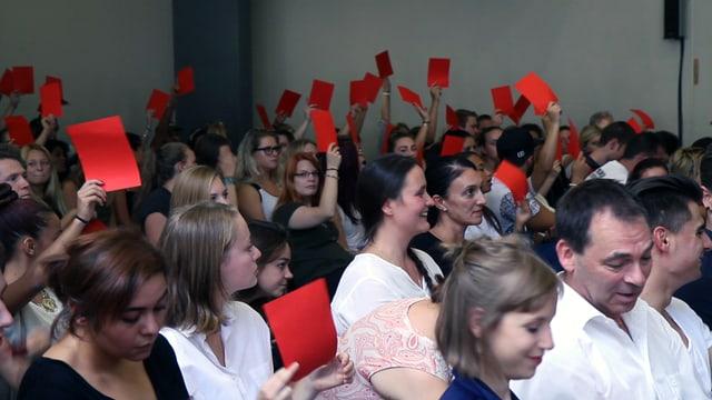 Jugendliche halten rote Abstimmungszettel in die Luft.