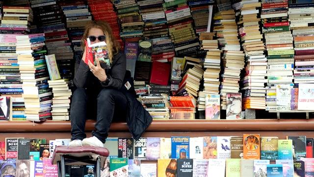 Frau sitzt auf Brüstung vor Strassenbuchladen und liest.
