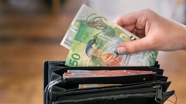 Hand steckt Banknoten ins Portemonnaie
