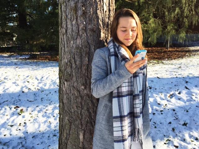 Ein Mädchen lehnt an einem Baum, ein Smartphone in der Hand.