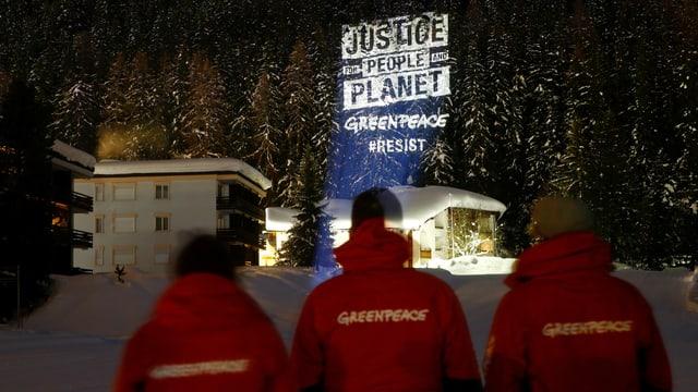 Drei Aktivisten schauen auf Projektion. Es steht: Justice, People, Planet.