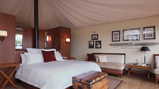 Ein Hotzelzimmer mit einem grossen Doeppelbett mit weissem Bettbezug unter einem zeltatrigen Dach und vielen Bildern an der Wand.