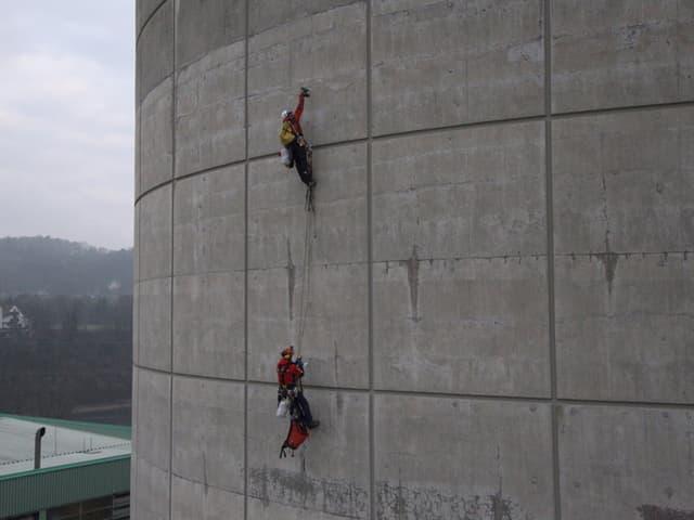 Aktivisten klettern an einem Turm hoch.