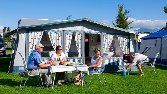 Drei ältere Personen sitzen an einem gedeckten Tisch vor einem Campingwagen-Vorzelt, ein weiterer bedient abseits den Gasgrill.